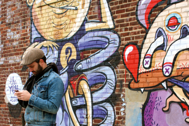 One of Brooklyn's many resident hipsters takes a break alongside some local street art.