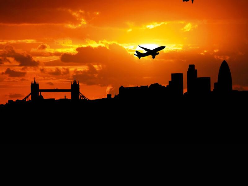 Jumbo jet flying over the London skyline.