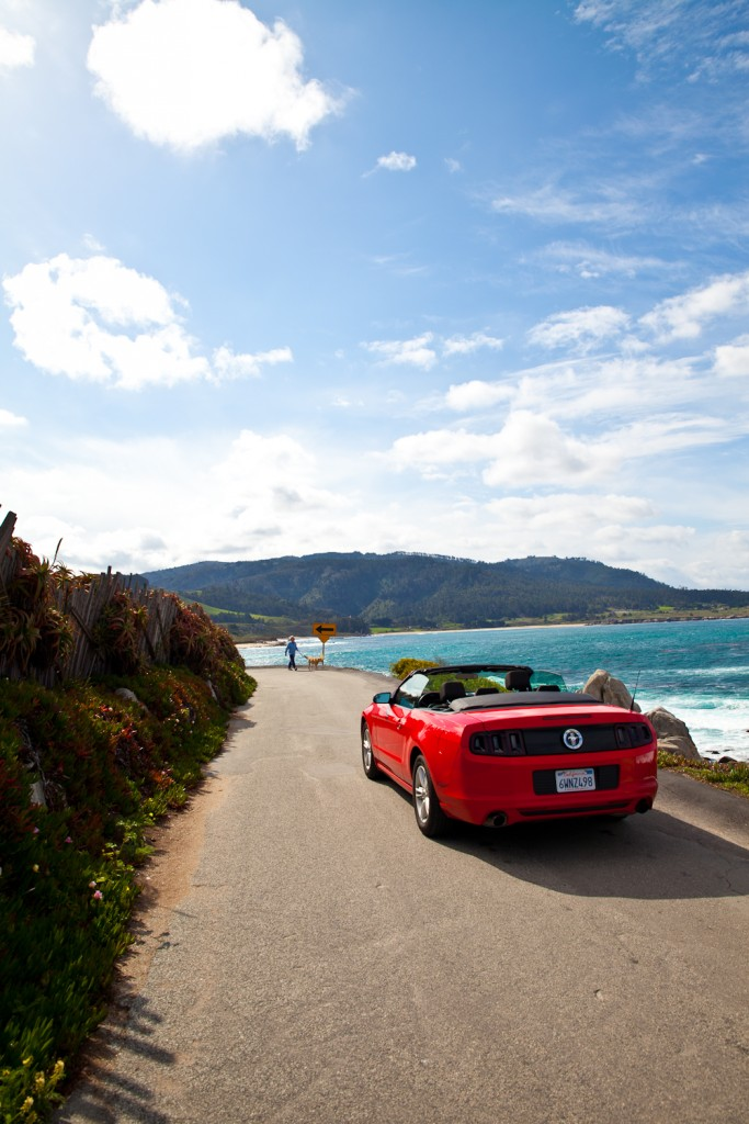 Driving along California's Pacific Coast Highway in a hot red convertible car.