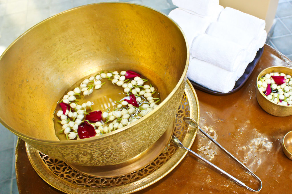 Alms bowl filled with lotus flower and rose petals.at Vana Bella, Thailand.