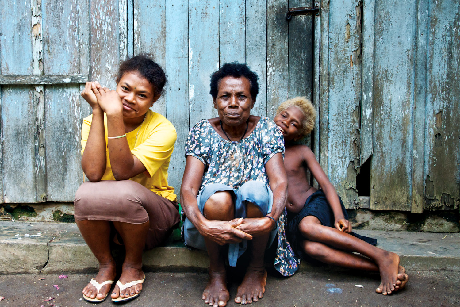 A Tolai woman and her grandchildren outside theirMaira home.