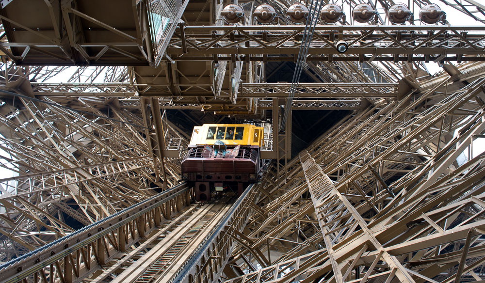 The lift of the Eiffel Tower taking patrons up to witness beautiful views of Paris from above