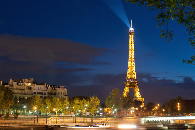 Experience the Eiffel Tower at night as it lights up Paris