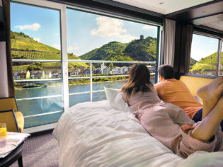 Couple looking out window of suite on river cruise in Europe