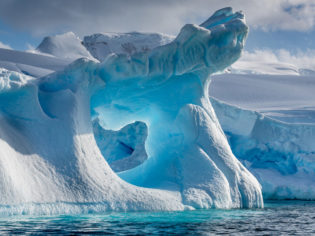 A dramatically shaped and weather eroded iceberg floating in Wilhemina Bay Antarctica